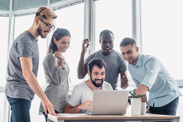 Geschäftsleute stehen über laptop am tisch im büro
