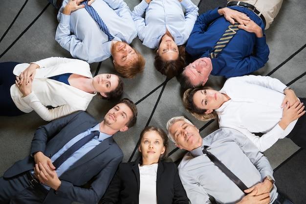 Geschäftsleute team ruhen auf boden in kreis