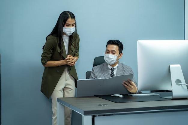 Geschäftsleute tragen eine schützende gesichtsmaske, während sie während der coronavirus-epidemie zusammenarbeiten.