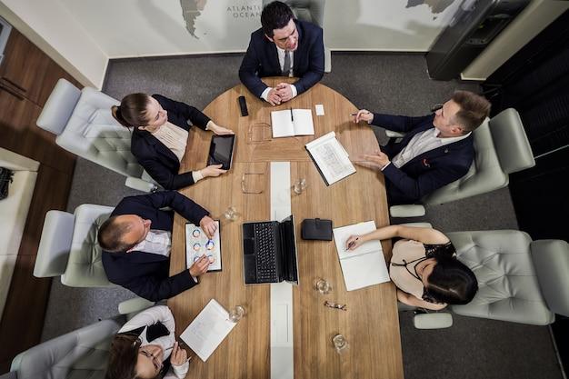 Geschäftsleute treffen konferenz diskussion unternehmenskonzept, geschäftsteam, geschäftspartner diskutieren dokumente und ideen, geschäftskonferenz in einem modernen büro, draufsicht