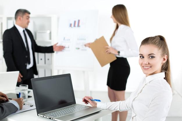Geschäftsleute treffen sich im büro, um das projekt zu besprechen. junge hübsche büroangestellte mit ihren kollegen. geschäftstreffen und teamwork-konzept
