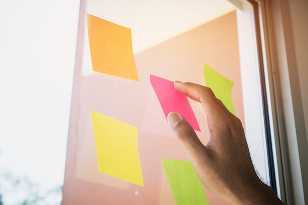 Geschäftsleute übergeben klebriges briefpapier des beitrags auf glasanzeigenzeitplanbrett