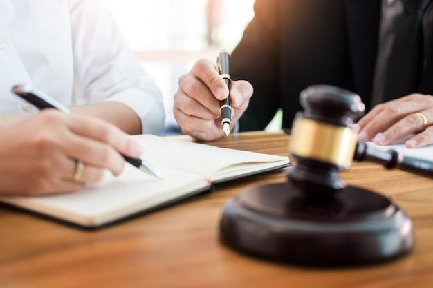 Geschäftsleute und anwälte diskutieren vertragsunterlagen am tisch. rechtskonzepte, beratung, juristische dienstleistungen