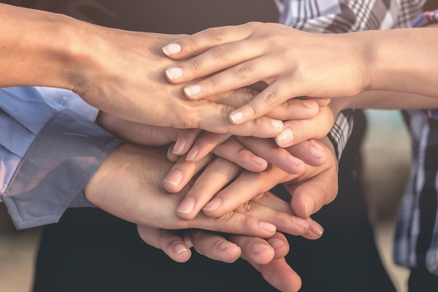 Geschäftsleute und architekten schließen sich den händen für teamwork, einheit und nachhaltigkeit an.