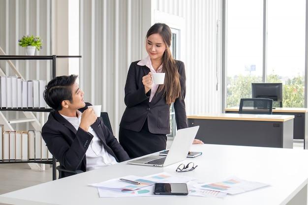 Geschäftsleute und frauen halten eine weiße kaffeetasse während der pause im büro.