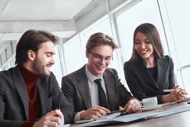 Geschäftsleute und geschäftsfrau im büro arbeiten zusammen am tisch sitzen mann mit brille spielen online-spiel auf dem smartphone, während kollegen ihn fröhlich lächelnd ansehen