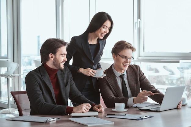 Geschäftsleute und geschäftsfrau im büro arbeiten zusammen frau servieren heißen kaffee, während männer am tisch sitzen und auf den laptop schauen und online-videos freudig lächeln
