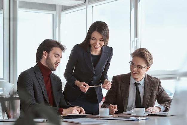 Geschäftsleute und geschäftsfrau im büro arbeiten zusammen sekretärin, die einen stift hält, der freundlich lächelt und den mann ansieht, der eine vereinbarung unterzeichnet