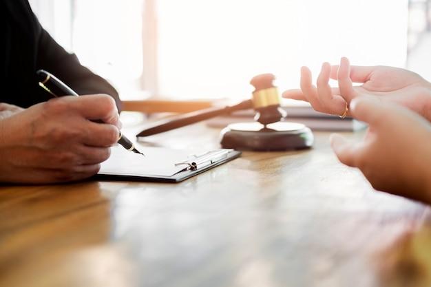 Geschäftsleute und rechtsanwälte, welche die vertragspapiere sitzen am tisch besprechen. rechtskonzepte, beratung, juristische dienstleistungen