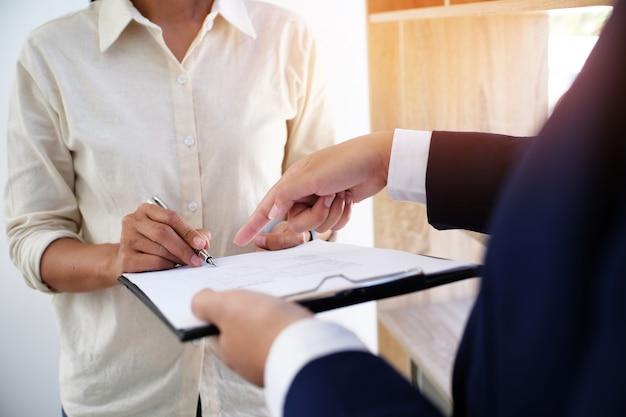 Geschäftsleute unterzeichnen vertrag, der einen vertrag mit immobilienmakler-konzept für berater- und hausversicherungskonzept abschließt.