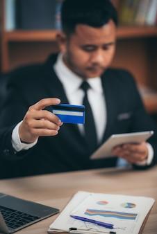 Geschäftsleute verwenden kreditkarten, um finanztransaktionen bei der arbeit durchzuführen