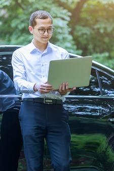 Geschäftsleute verwenden laptops neben außenfahrzeugen