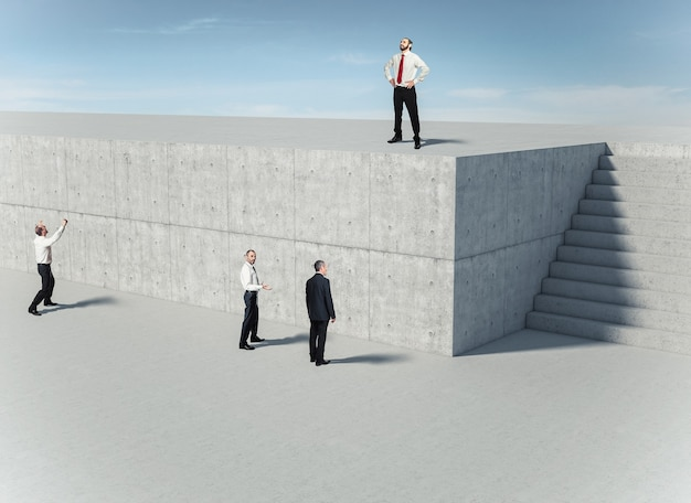 Geschäftsleute vor einer betonmauer, einer von ihnen findet die lösung und benutzt die treppe. konzept von einfallsreichtum und problemlösung.