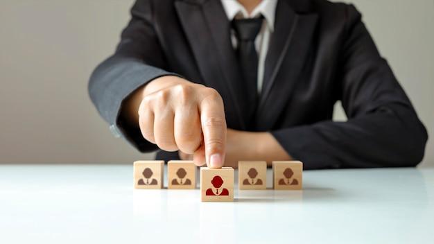 Geschäftsleute wählen holzklötze, die herausragende menschen aus der masse zeigen. oder als erfolgreicher teamleiter hr und ceo