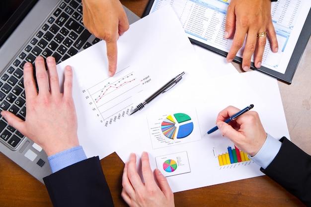 Geschäftsleute, welche die diagramme und diagramme zeigen die ergebnisse ihrer erfolgreichen teamarbeit besprechen