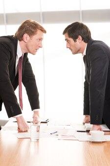 Geschäftsleute widersprüchlich. zwei junge männer in formeller kleidung, die sich gegenüberstehen, während sie von angesicht zu angesicht stehen