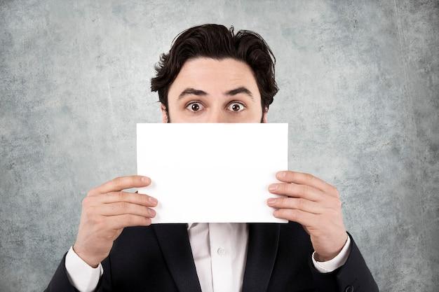 Geschäftsleute zeigen ein weißes blatt papier vor gesicht auf einer betonwand. werbefläche.