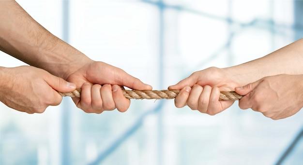 Geschäftsleute ziehen seil in entgegengesetzte richtungen
