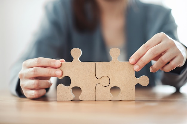 Geschäftslösungen partnerschaft und strategiekonzept, geschäftsfrau hand, die puzzle auf schreibtisch verbindet.