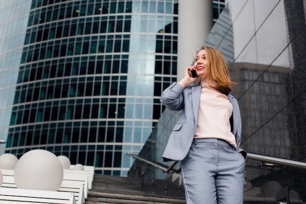 Geschäftsmädchen, das am telefon am bürogebäude in der stadt spricht.