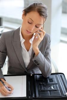 Geschäftsmädchen, das am telefon spricht und kenntnisse nimmt