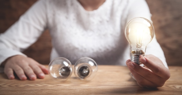 Geschäftsmädchen, das glühbirne hält. kreativität