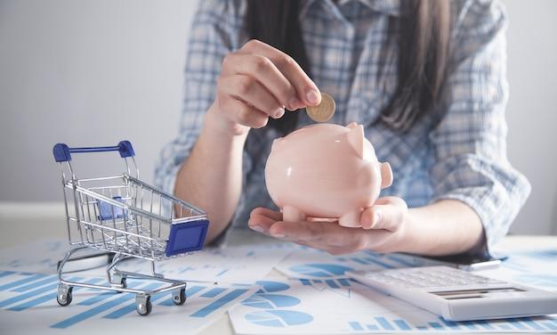 Geschäftsmädchen, das münze in ein sparschwein setzt