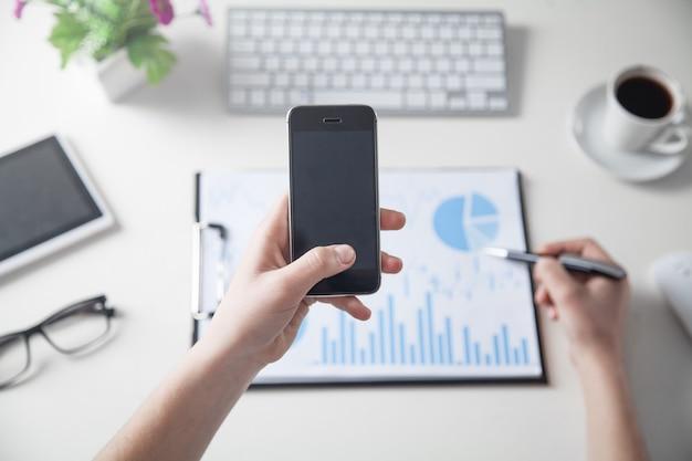 Geschäftsmädchen, das smartphone mit finanzgraphen im schreibtisch verwendet. im büro arbeiten