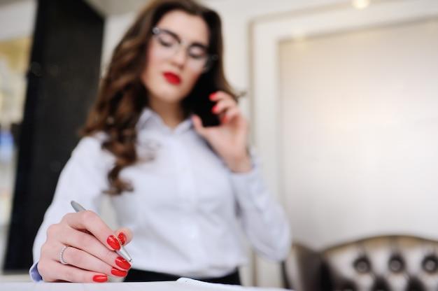 Geschäftsmädchen in einem weißen hemd und in einer brille macht notizen in einem notizbuch und spricht auf einem mobiltelefon