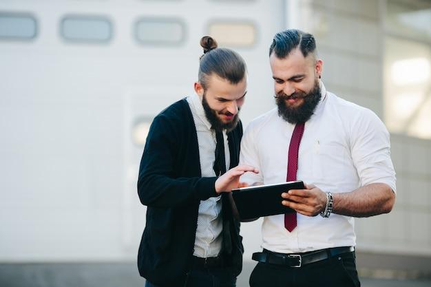 Geschäftsmänner bei einer tablette suchen