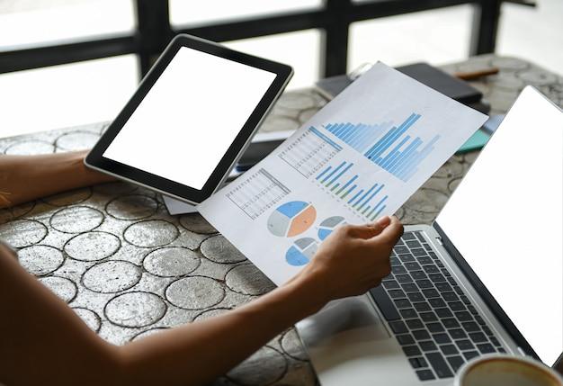 Geschäftsmänner, die an hand diagramm und tablette halten er überprüft die unternehmensinformationen.