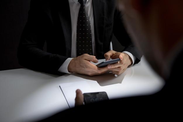 Geschäftsmänner, die auf smartphone bei der sitzung simsen