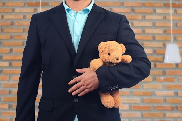 Geschäftsmänner, die ein bärenspielzeug auf backsteinmauer halten