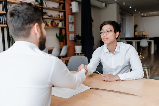 Geschäftsmänner, die hände auf einem abkommen arbeitet in einer unternehmenszentrale rütteln