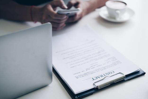 Geschäftsmänner, die smartphone beim sitzen am schreibtisch mit vertragspapier, laptop-computer verwenden