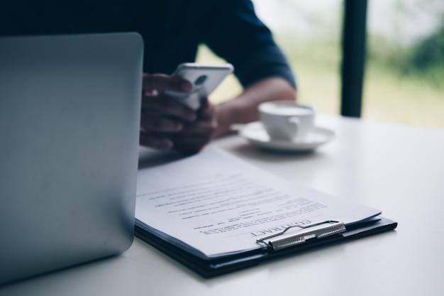 Geschäftsmänner, die smartphone beim sitzen am schreibtisch mit vertragspapier verwenden