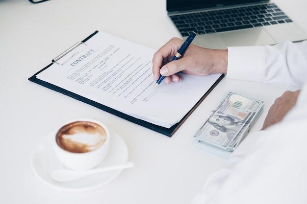 Geschäftsmänner, die stift halten, um geschäftsdokument und vertragsblatt zu schreiben