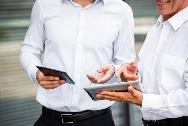 Geschäftsmänner, die tabletten betrachten