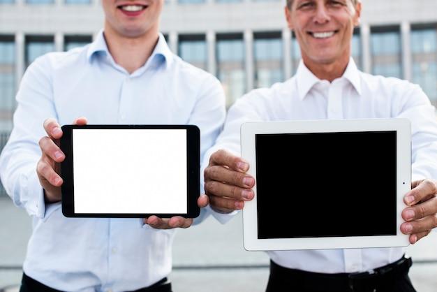 Geschäftsmänner, die tablettenmodell halten