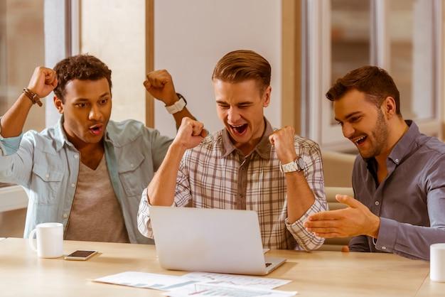 Geschäftsmänner jubeln zu und benutzen laptop beim arbeiten.