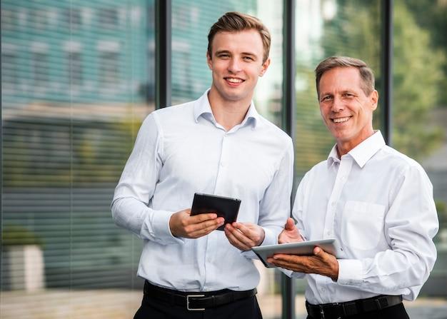 Geschäftsmänner mit den tabletten, die kamera betrachten