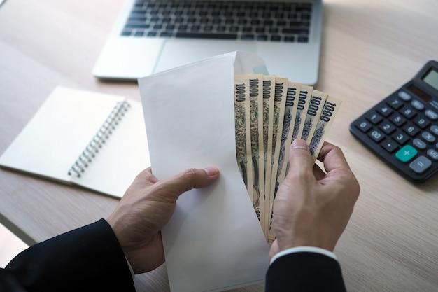 Geschäftsmänner öffnen einen gehaltsumschlag, der eine banknote des japanischen yen im büro ist.