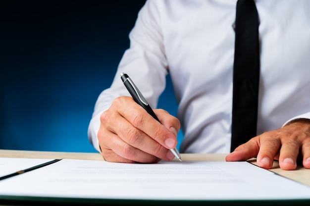 Geschäftsmanager, der ein dokument in einem ordner auf seinem schreibtisch signiert. über dunkelblauem hintergrund.