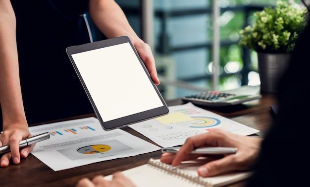 Geschäftsmanager, der tablett leeren bildschirm und besprechung auf dem tisch im büro hält