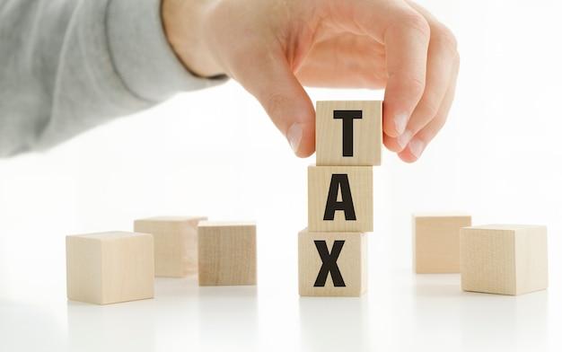 Geschäftsmann am schreibtisch im büro zeigen sie einen holzwürfel mit dem wort steuer auf unternehmensinvestitionen.