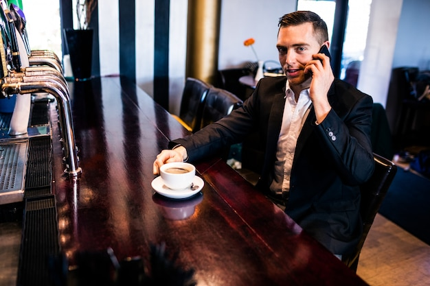 Geschäftsmann am telefon, das einen kaffee am zähler in einer bar trinkt