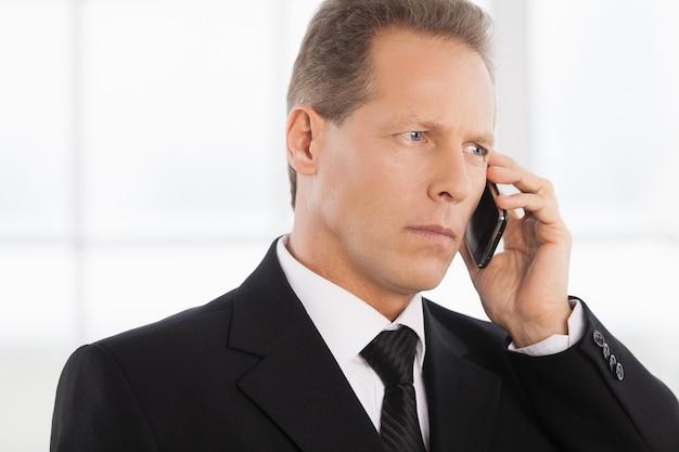 Geschäftsmann am telefon. porträt eines selbstbewussten reifen mannes in formeller kleidung, der telefoniert, während er in der nähe des fensters steht