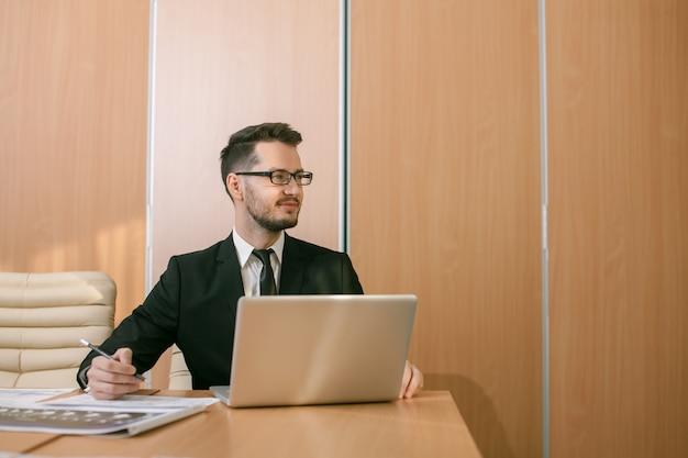 Geschäftsmann an einem arbeitsbereich, der tippt