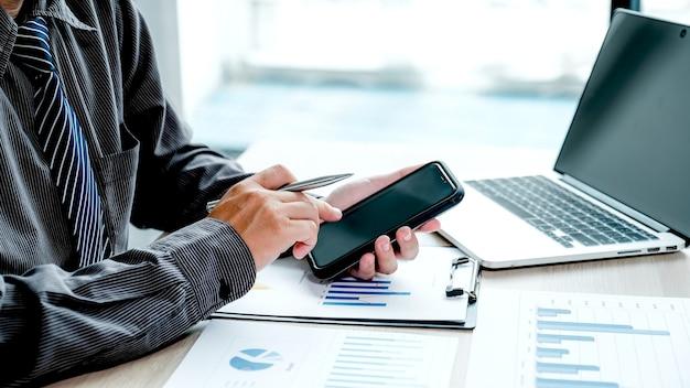 Geschäftsmann analysiert das diagramm mit laptop im büro, um anspruchsvolle geschäftsziele zu setzen