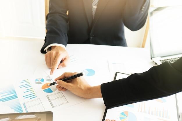 Geschäftsmann analysiert investitionstabellen und drückt taschenrechnertasten über dokumente. buchhaltungskonzept